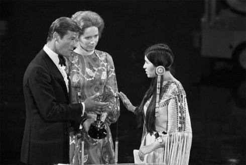 Momento en que la india  apache Sacheen Littlefeather, enviada por Marlon Brando rechaza,  en nombre de del actor,  el Oscar que le entregarían Roger Moore  y Liv Ullmann (sueca casualmente)